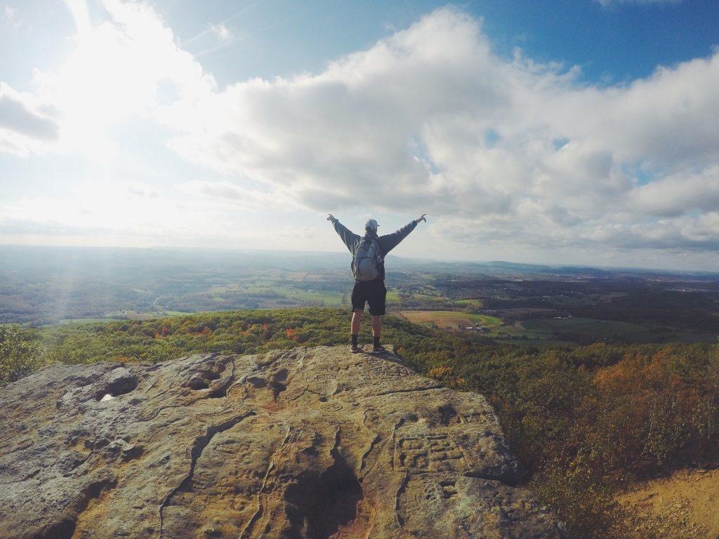 崖で両手を挙げる男性の後ろ姿