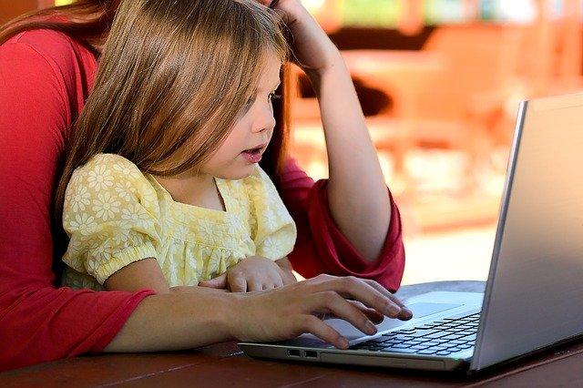抱っこされてPCの画面を見る女の子