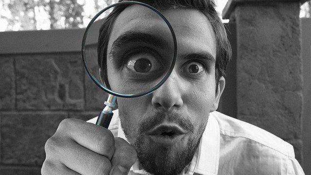 虫眼鏡でこちらを見る男性