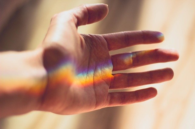 虹色の光があたっている手のひら